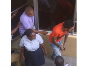 Vybz Kartel, seen here in an orange shirt and jeans was taken to a Kingston hospital Thursday morning after complaining of chest pains. Credits:   jamaica-gleaner.com